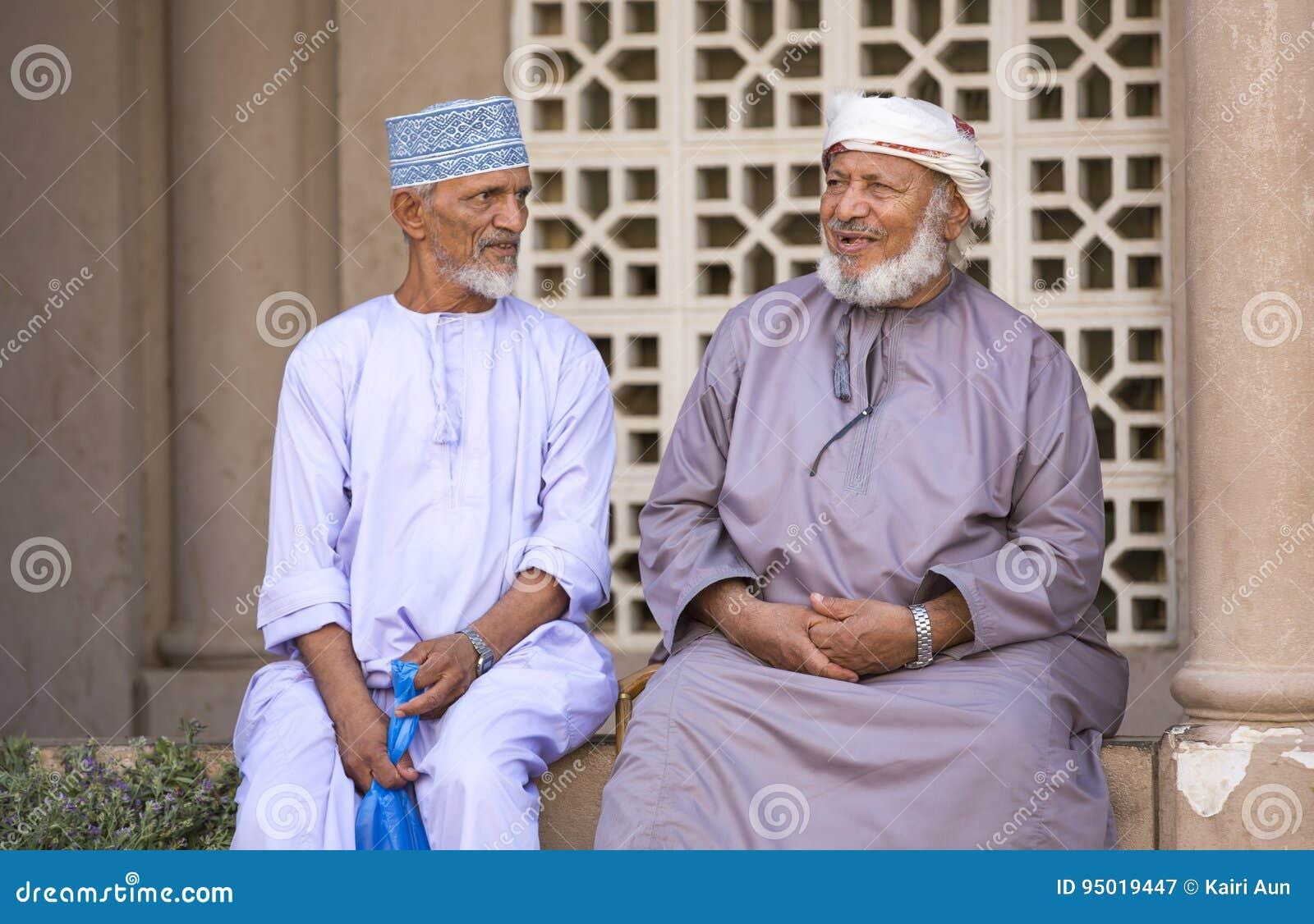 Due uomini dell Oman in abbigliamento tradizionale che chiacchierano ad una  vecchia via m. c8a667103f5