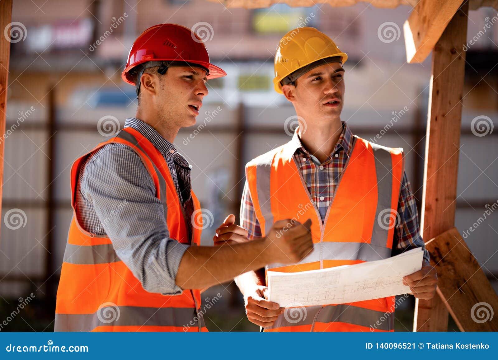 Due uomini vestiti in camice, nelle maglie arancio del lavoro ed in caschi esplorano la documentazione della costruzione sul cant