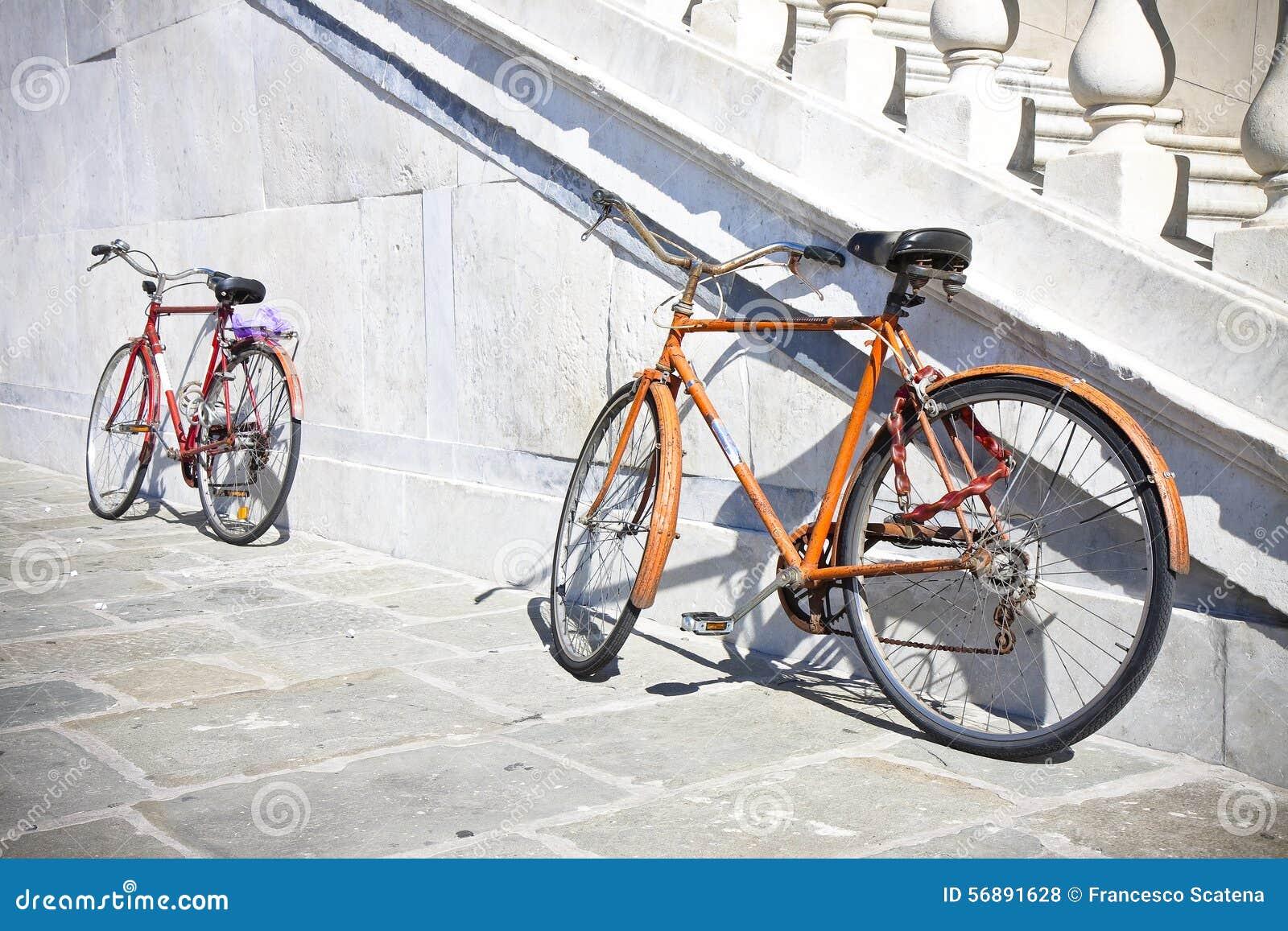 Due vecchie biciclette arrugginite contro una parete di marmo