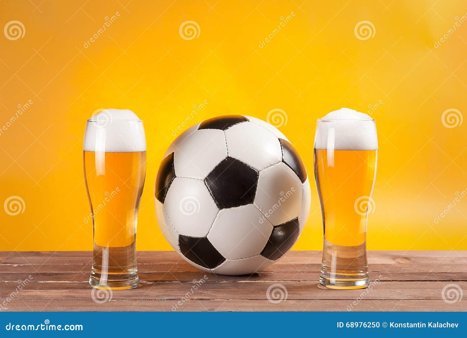 Due vetri con birra e pallone da calcio vicino alla ripresa esterna della TV