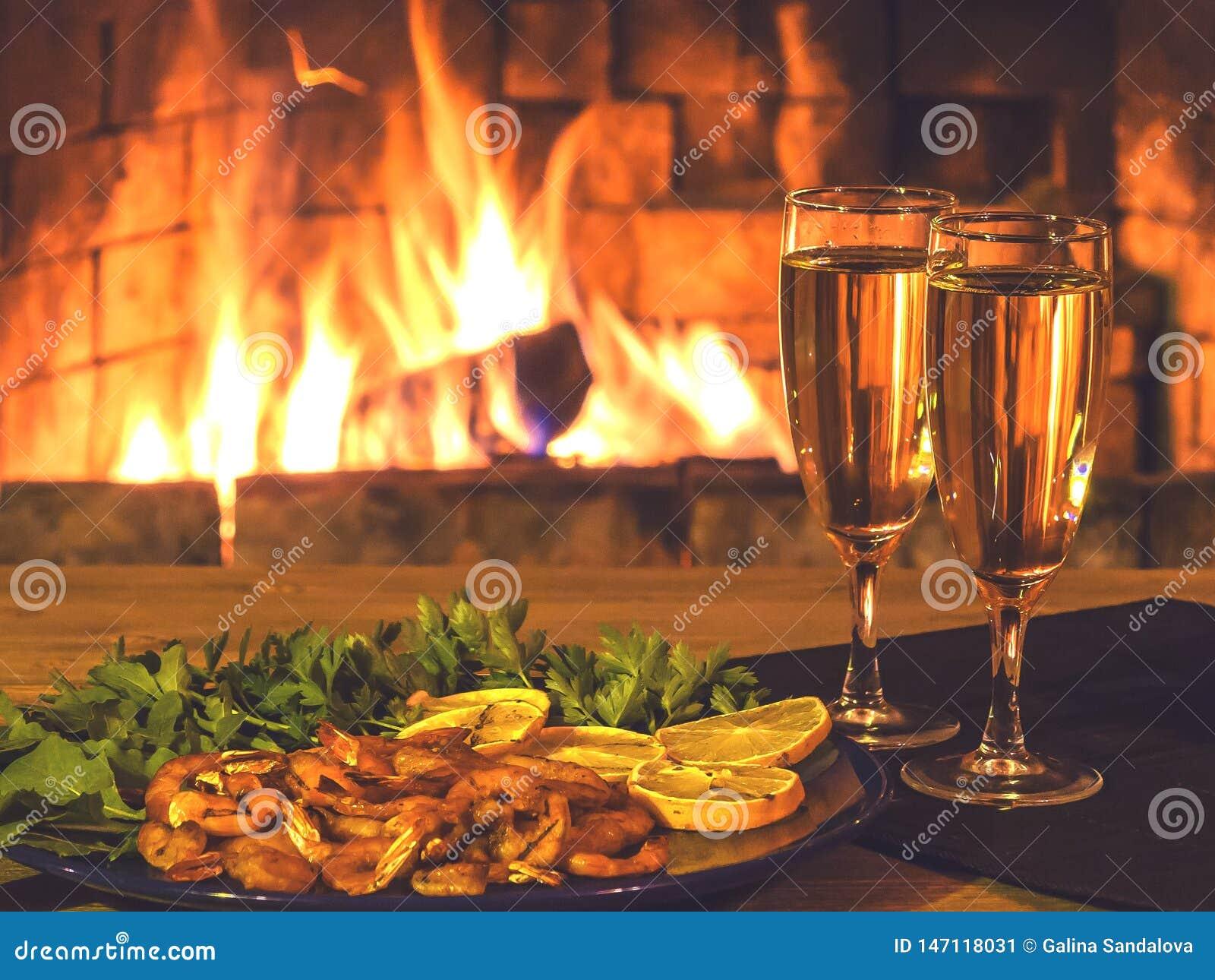 Due vetri con champagne e un piatto con i gamberetti, il limone ed i verdi su una tavola di legno contro lo sfondo della a