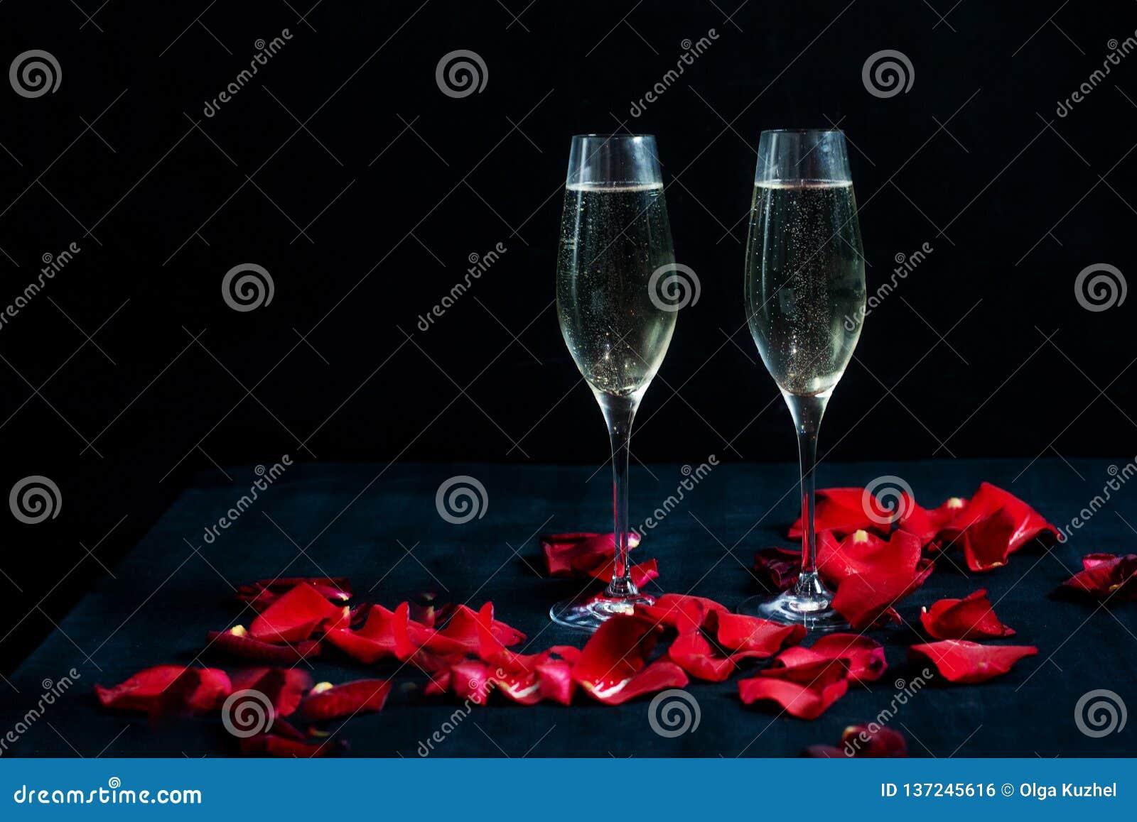 Due vetri con champagne ed i petali bianchi delle rose rosse sui precedenti neri