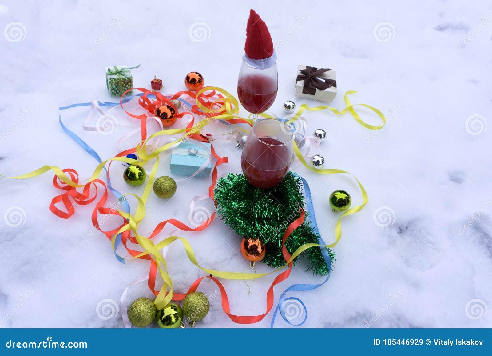 Due vetri con vino rosso sulla tavola di legno con i fairylights e la carta di Buon Natale