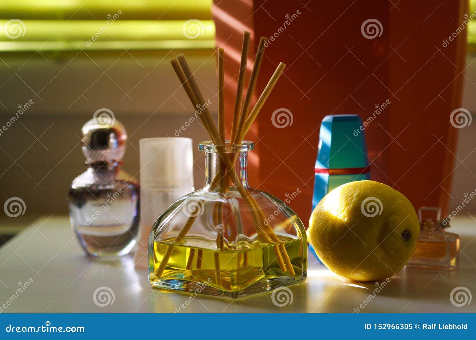 Duftbelüfterglas mit Reedstöcken zwischen Parfüm flacons, die natürlichen Geruch der Zitrone geben