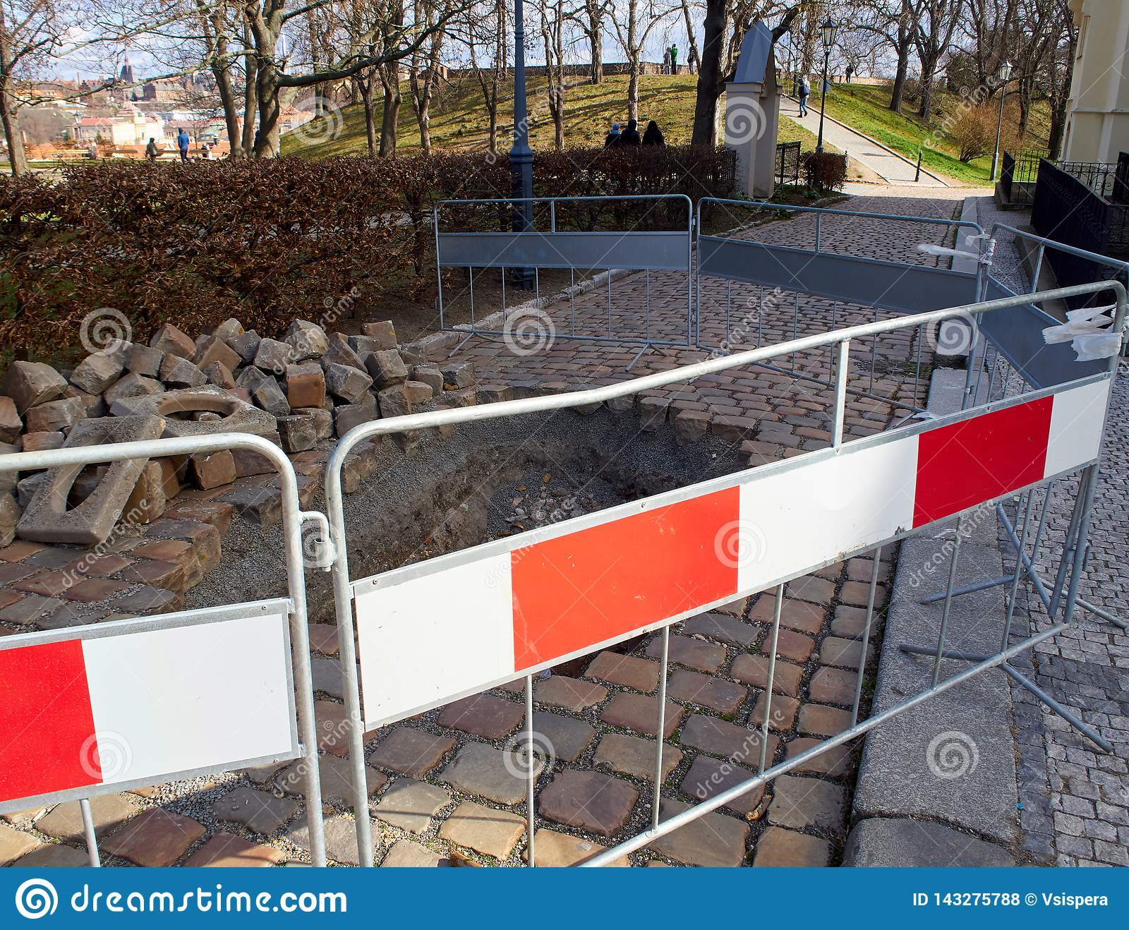 Dugged walkway and hole in the pavement. The protection block. Park with trees