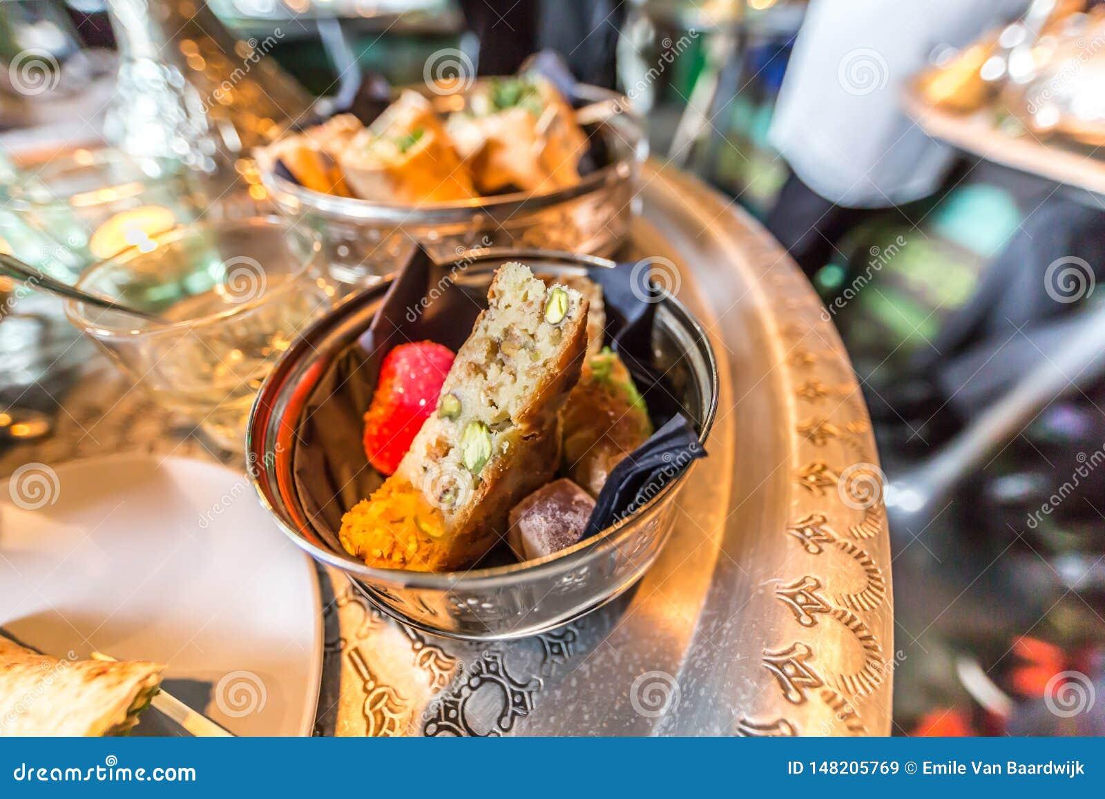 Dulces marroquíes deliciosos en un bol de vidrio en una bandeja de cobre
