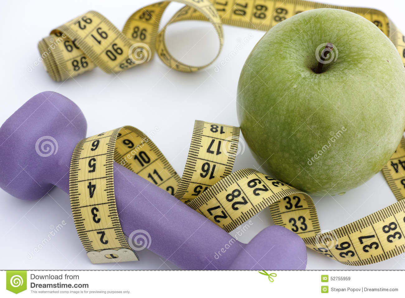 Dumbbell and green apple with tape measure stock photo