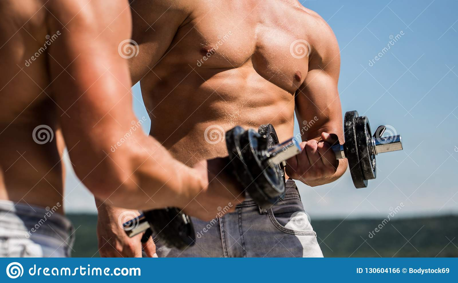 Dumbbell. Muscular bodybuilder guys, exercises with dumbbells. Strong bodybuilder, perfect deltoid muscles, shoulders