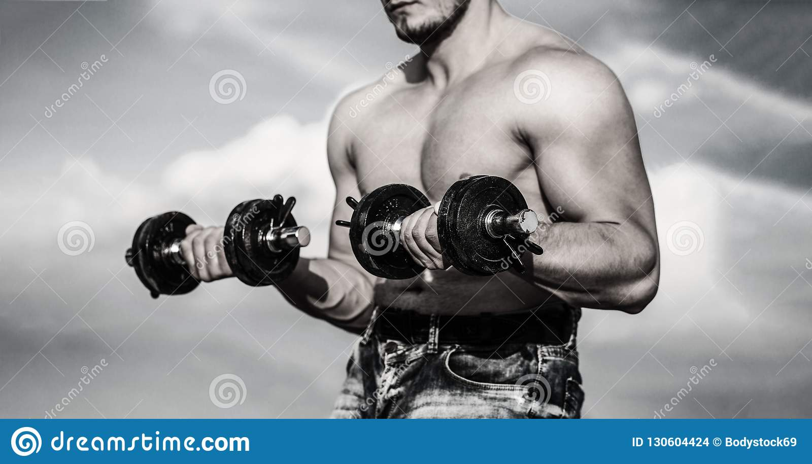 Dumbbell. Strong bodybuilder, perfect deltoid muscles, shoulders, biceps, triceps and chest. Muscles with dumbbell. Man