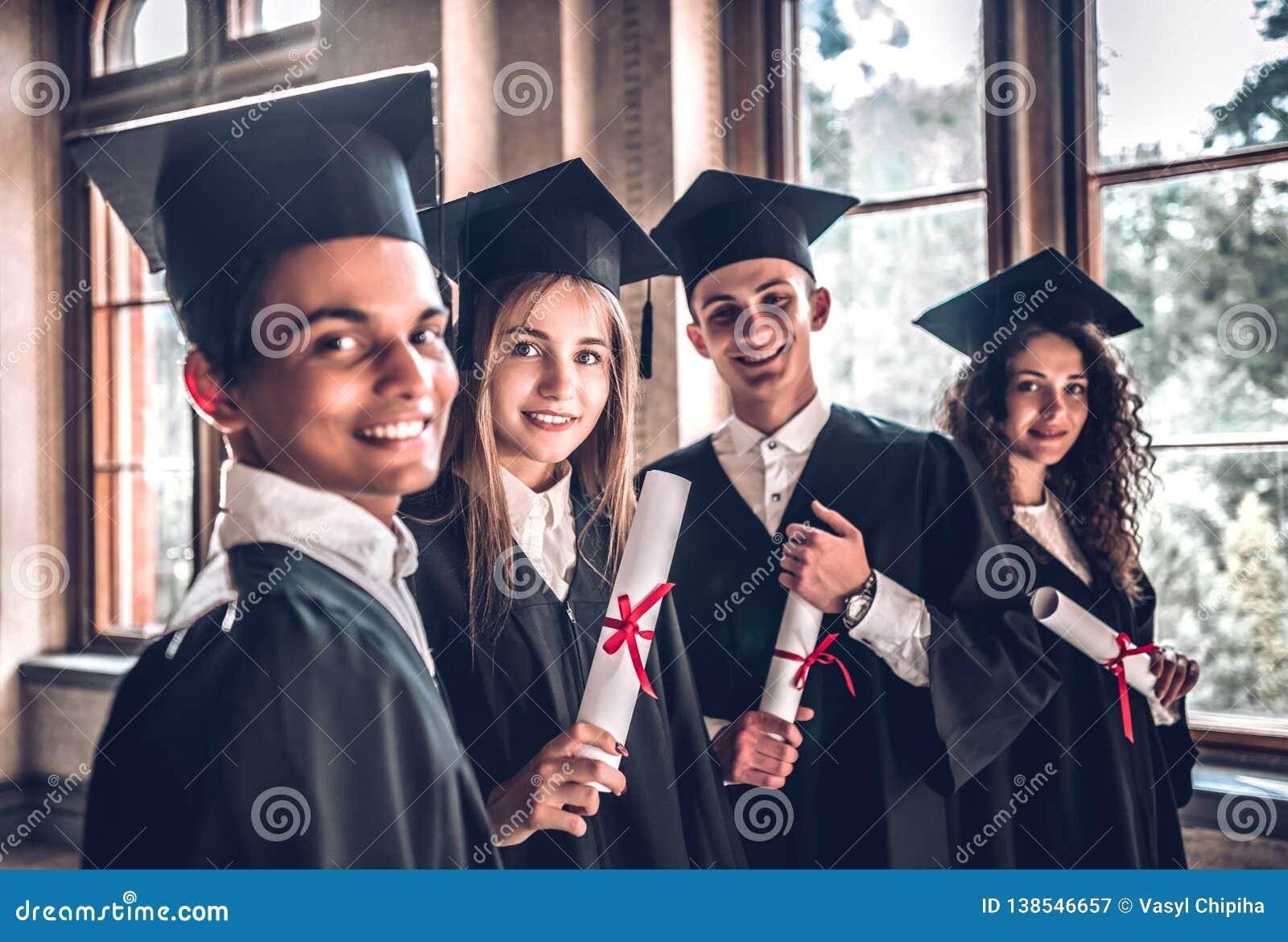 Dumny być absolwentami Grupa uśmiechnięci szkoła wyższa absolwenci stoi wpólnie w uniwersyteckiej i ono uśmiecha się patrzeje kam