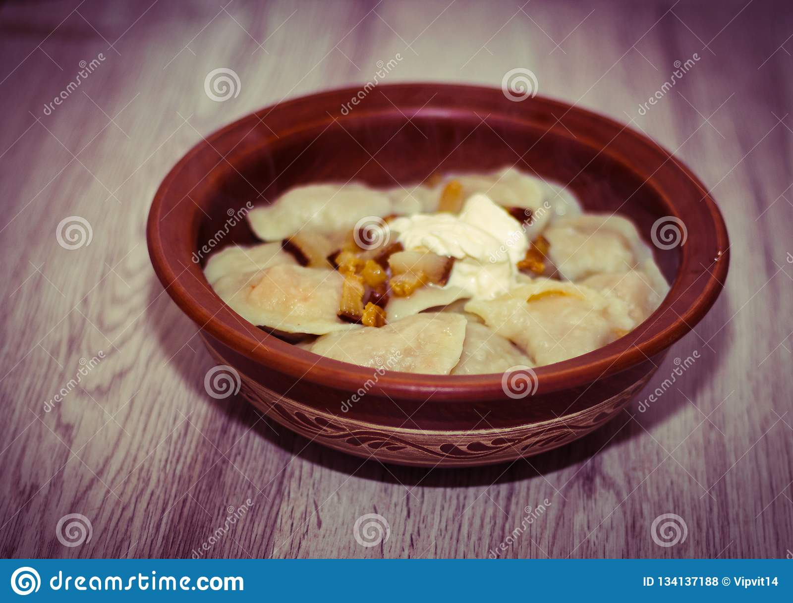 Dumplings in a clay plate on the wooden table. Dumplings, filled with mashed potato. Varenyky, vareniki, pyrohy -