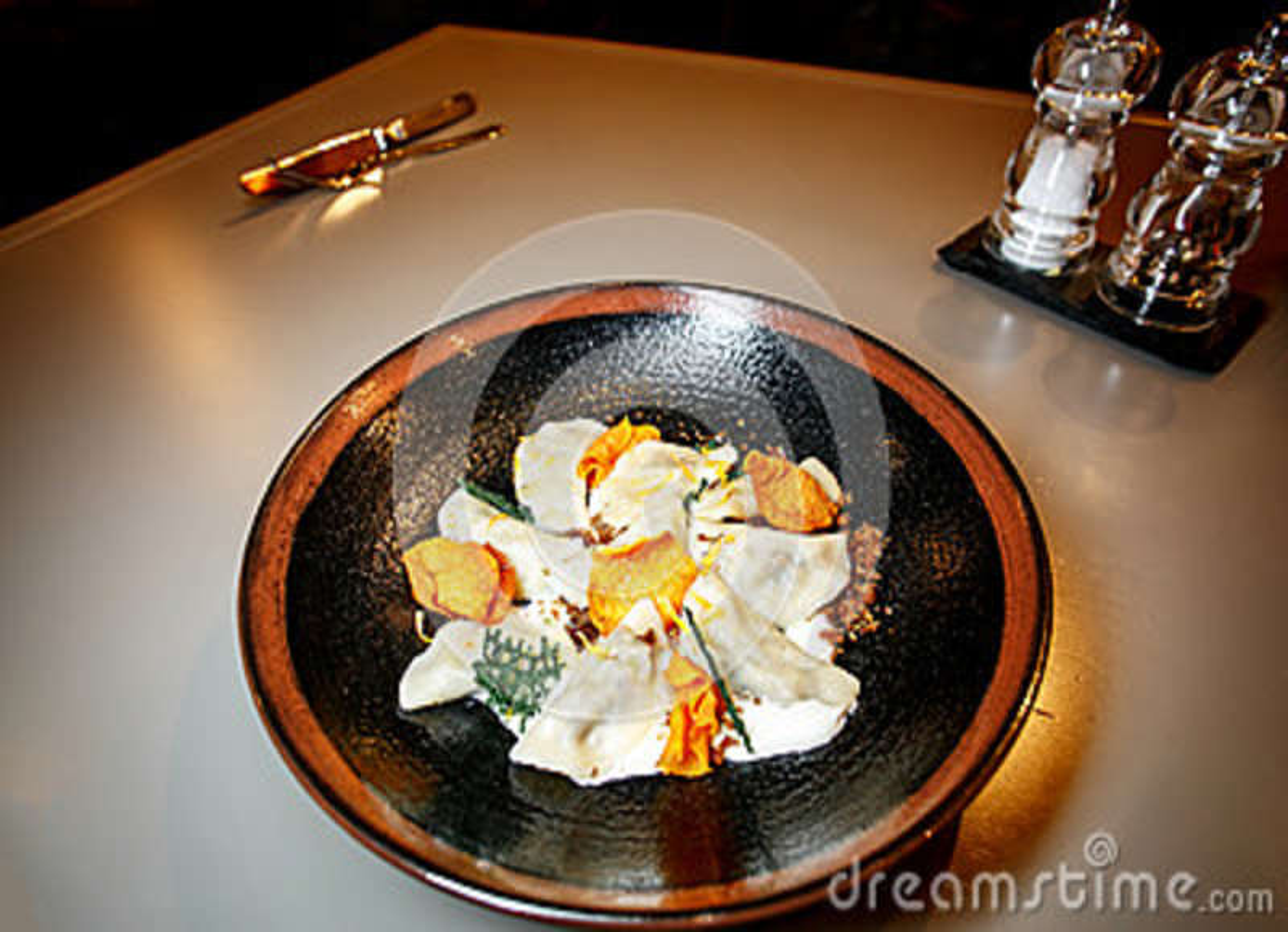 Dumplings, homemade ravioli in a plate on black background