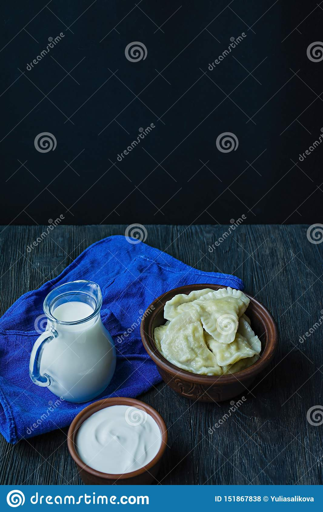 Dumplings with potatoes and cabbage. Sour cream, milk and greens. Traditional dish of Ukraine. Dark wooden background