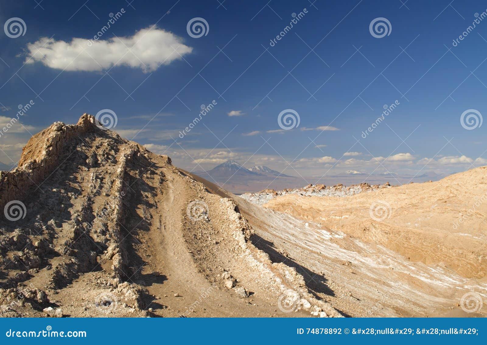 Dunas de areia rochosas, hostis que conduzem ao vulcão dois na distância no vale da lua, deserto de Atacama