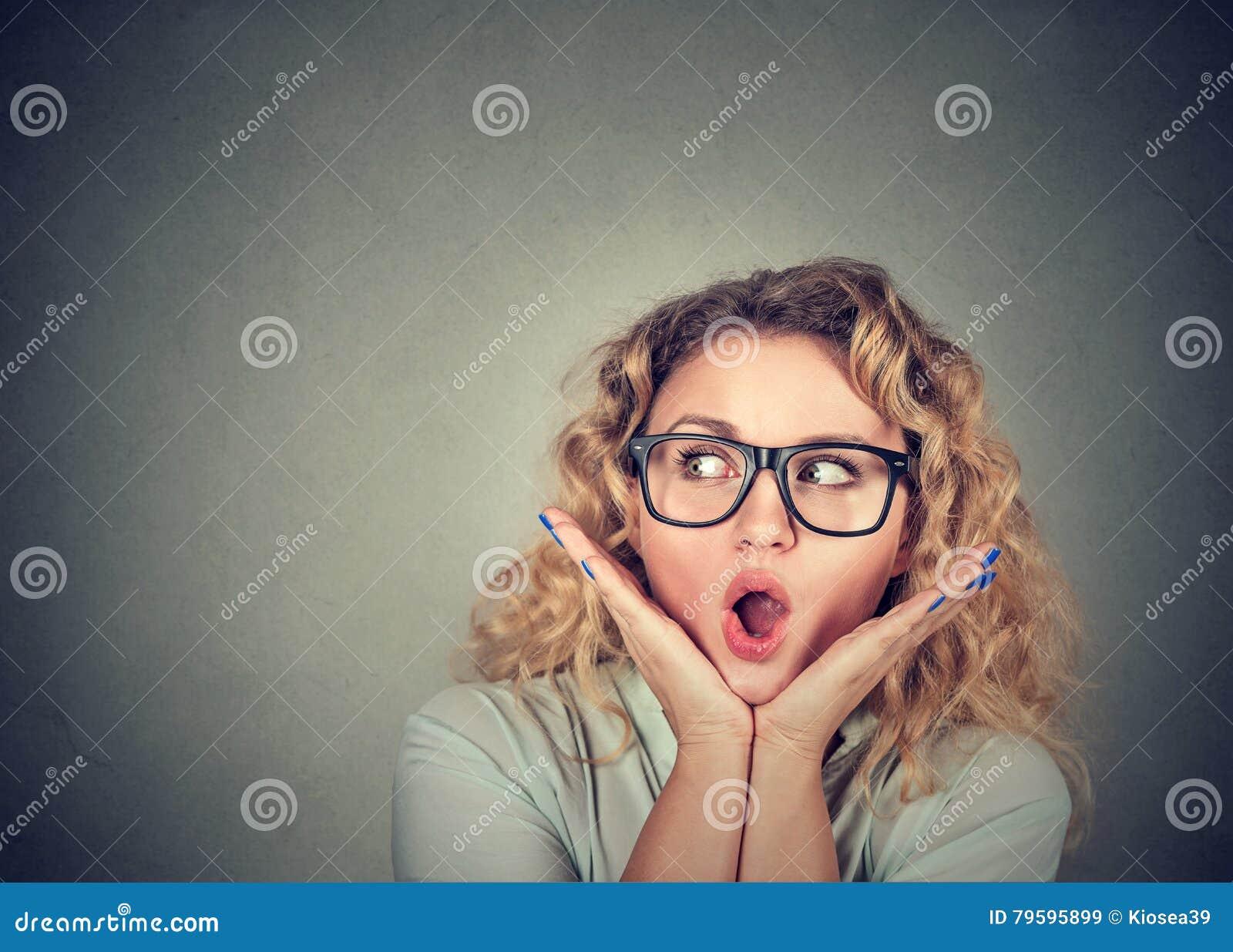 Dundersuccé kvinna som ser det upphetsade innehavet hennes öppnade mun