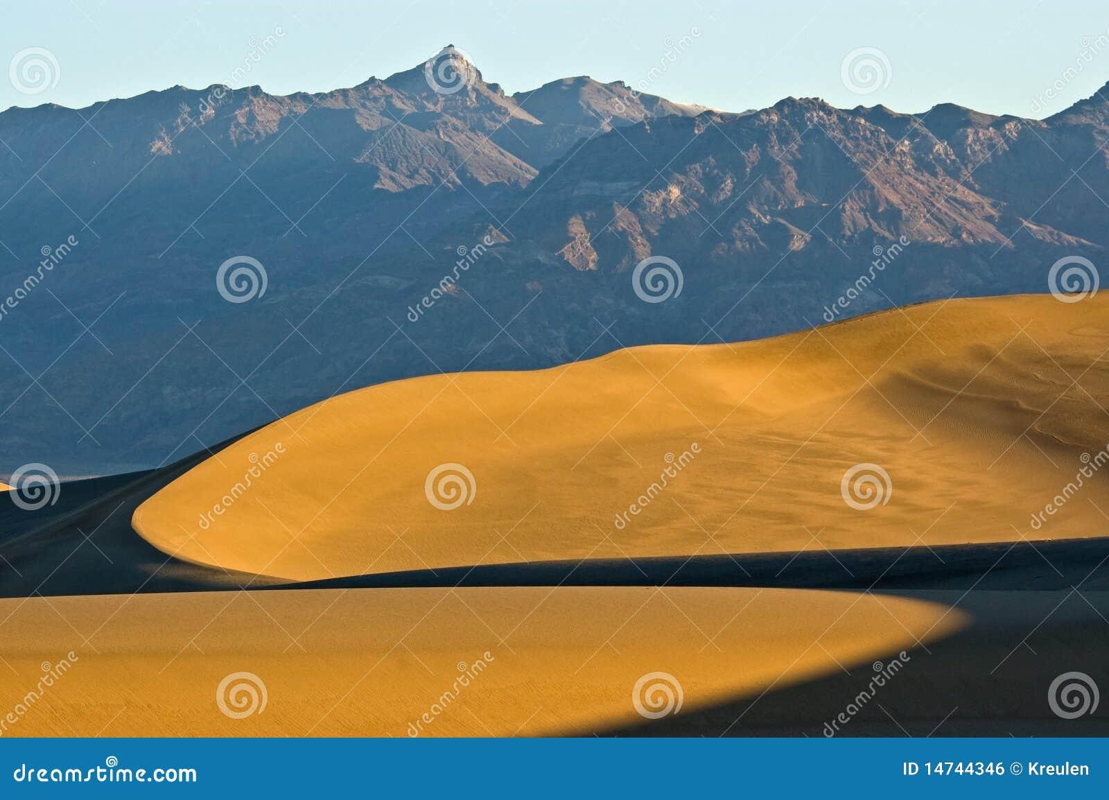 dune di sabbia curve sotto la montagna immagine stock