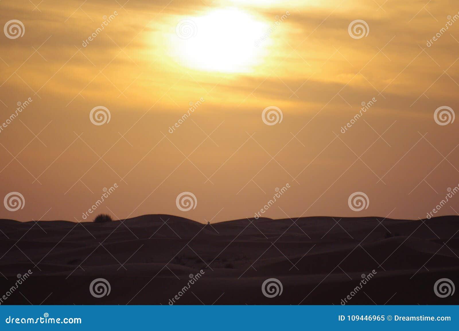 Dunes de désert au coucher du soleil avec le nuage