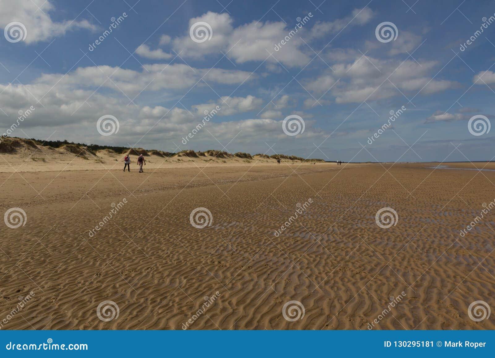 Dunes et personnes de sable marchant sur la plage à la Wells-prochain-le-mer