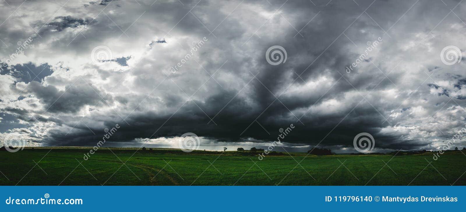Dunkles Sturmwolkenpanorama über der grünen Rasenfläche