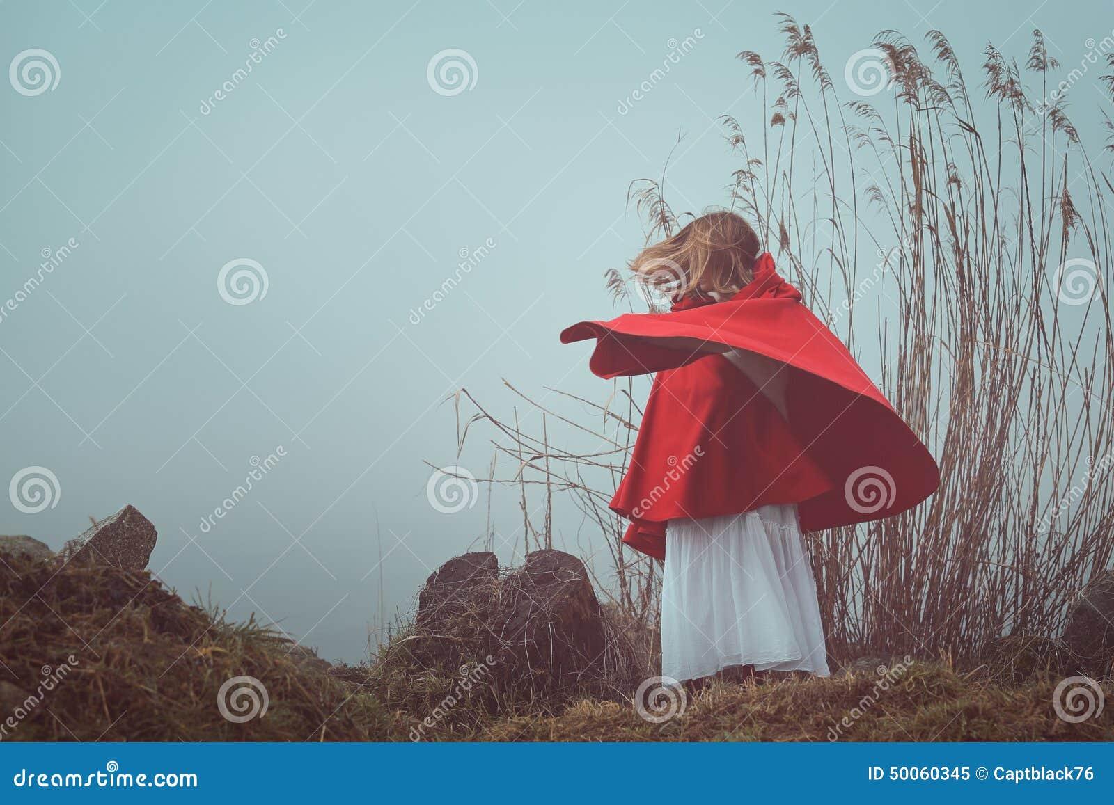 Dunkles und surreales Porträt einer roten mit Kapuze Frau