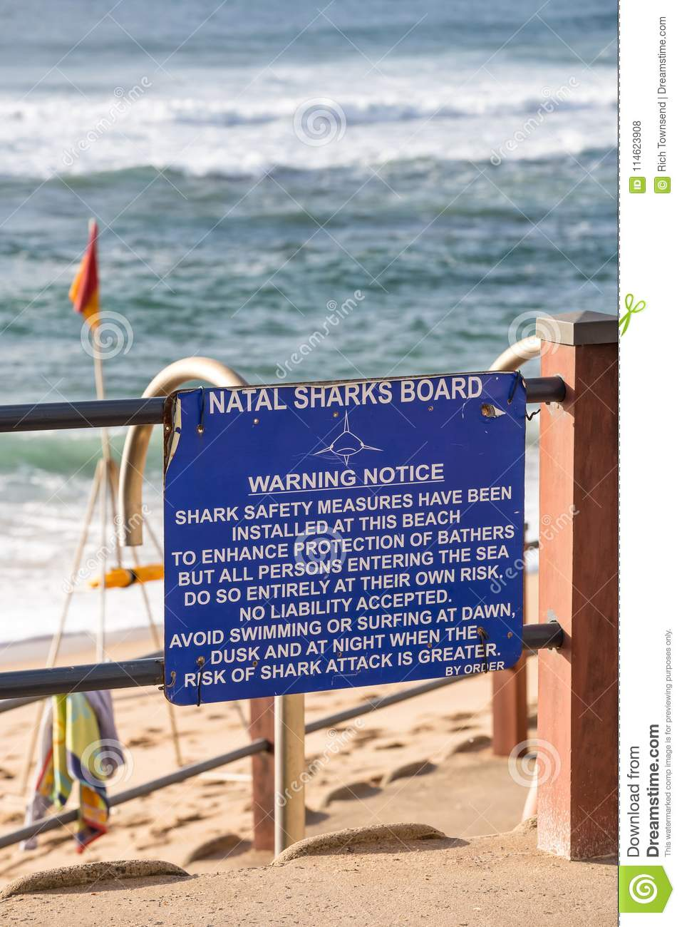 Shark protection notice on beachfront.