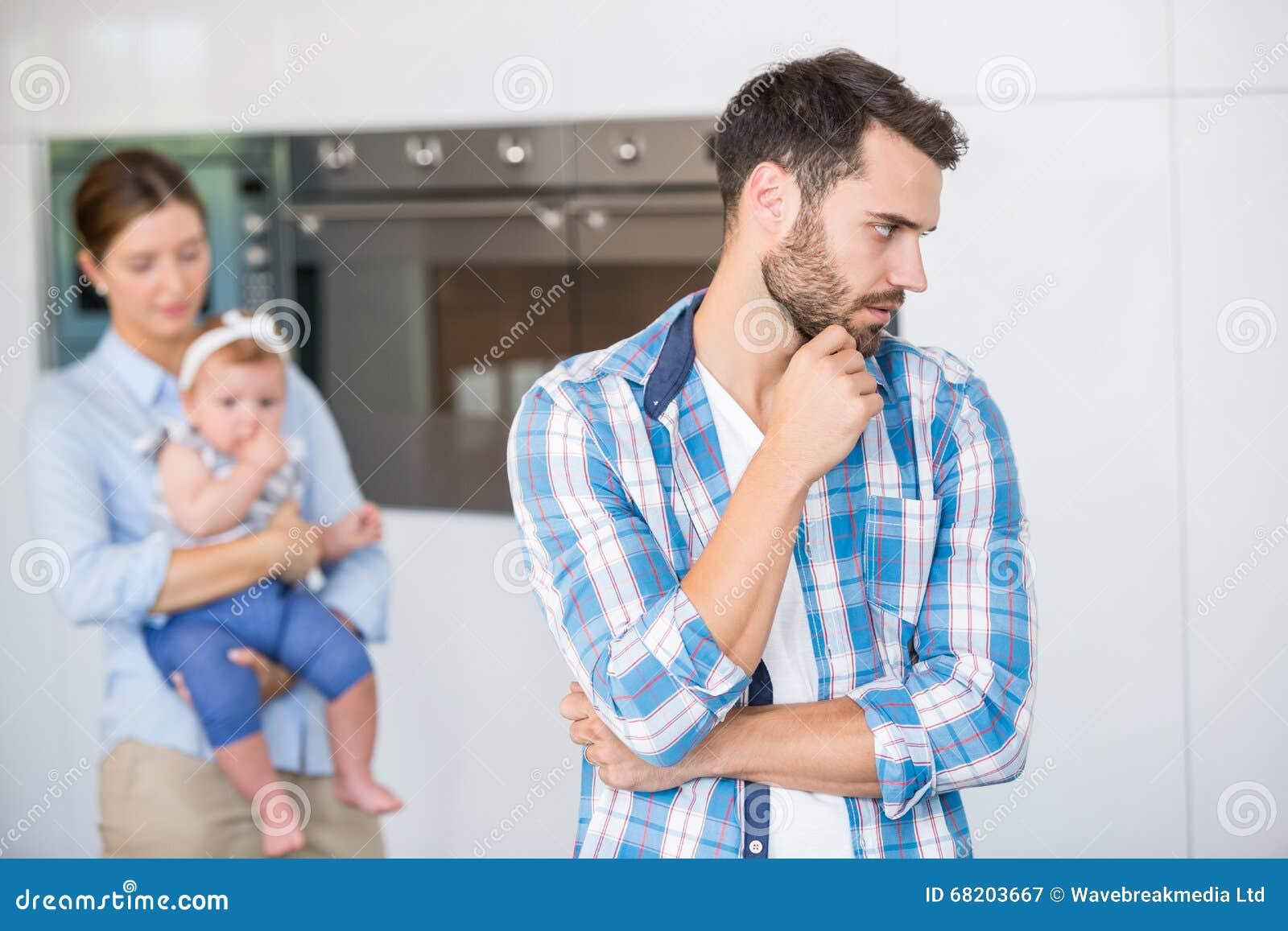 Durchdachter Mann Mit Frau Und Baby Im Hintergrund