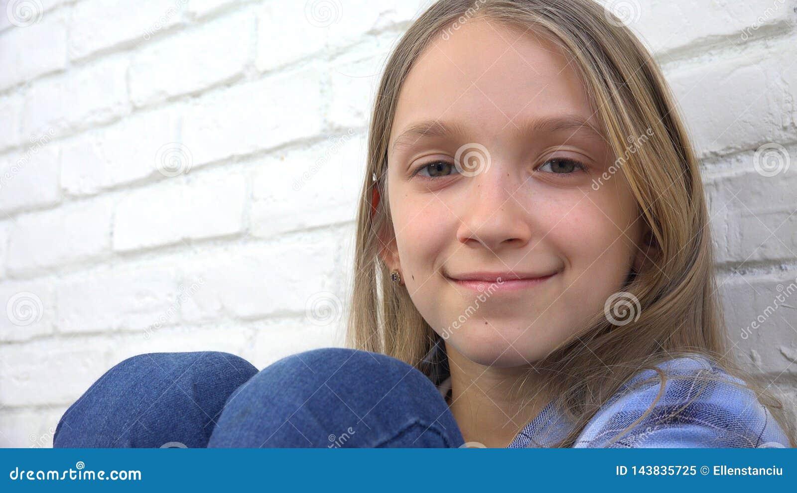 Durchdachtes Kinderporträt, lächelndes Kindergesicht, das in camera blondes gebohrtes Mädchen schaut