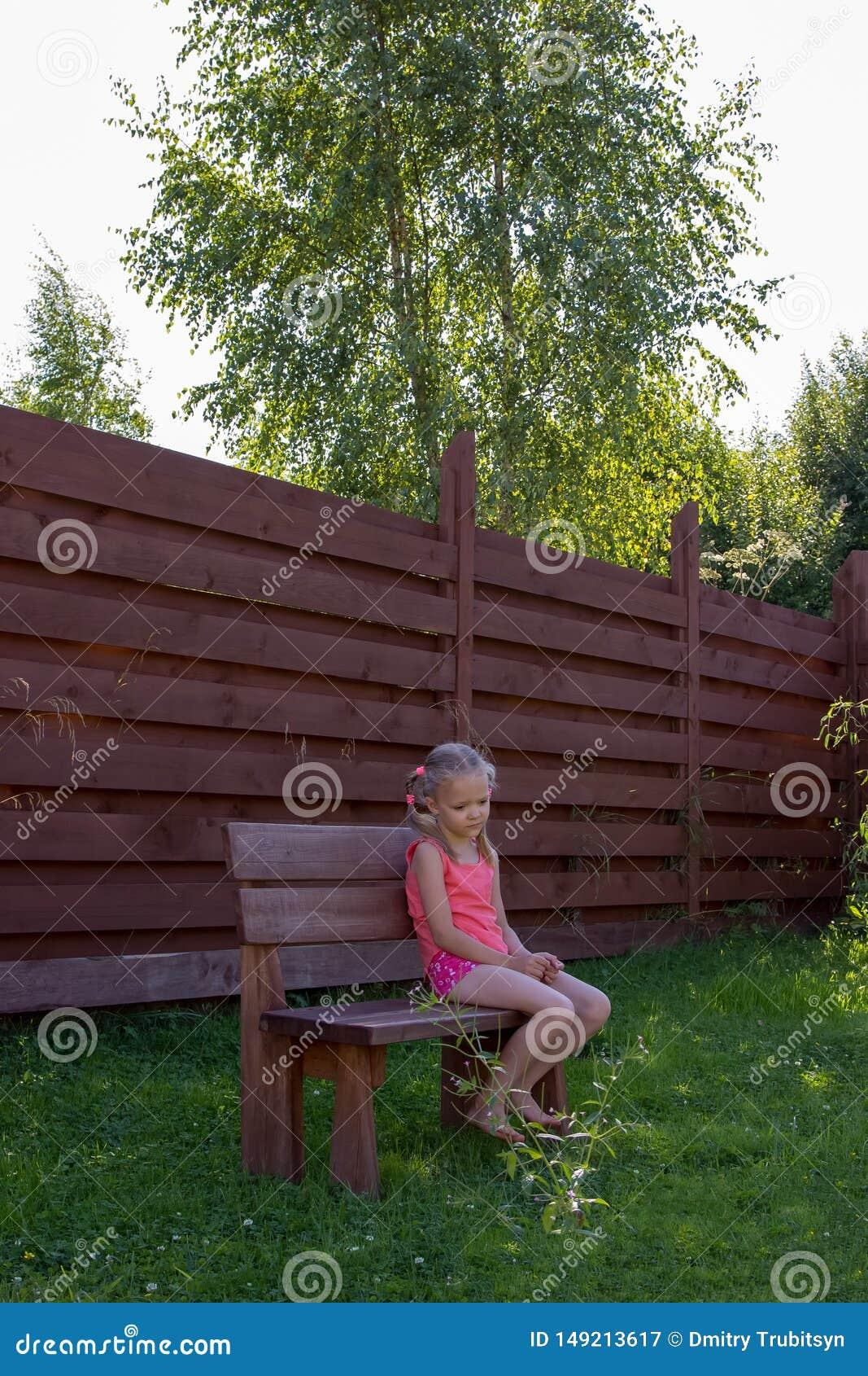 Durchdachtes M?dchen, das auf Holzbank sitzt