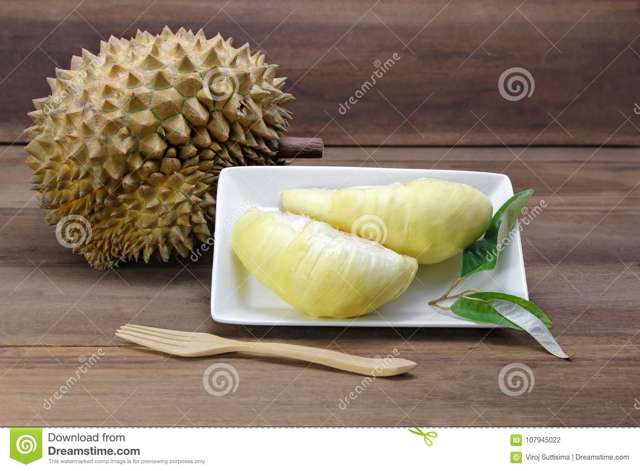 Durian fruits and yellow flesh durian on white dish with durian leaf, wooden background.