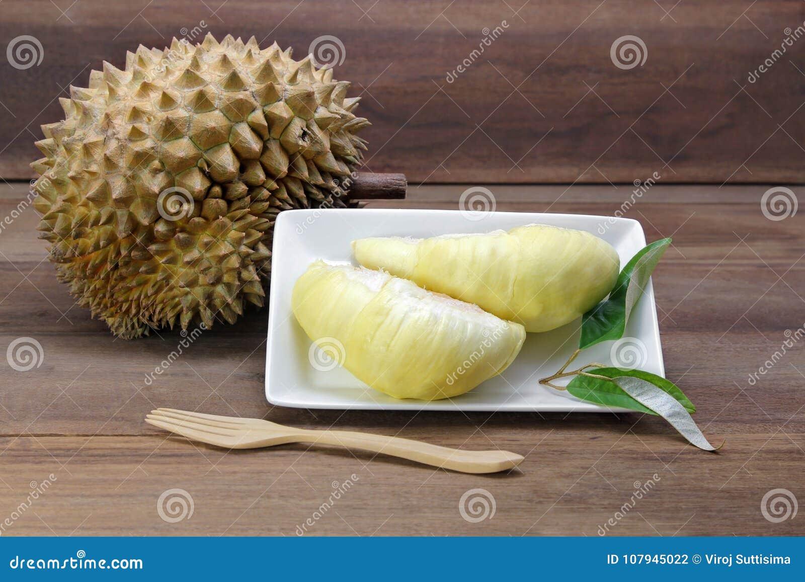 Durianvruchten en geel vlees durian op witte schotel met durian blad, houten achtergrond