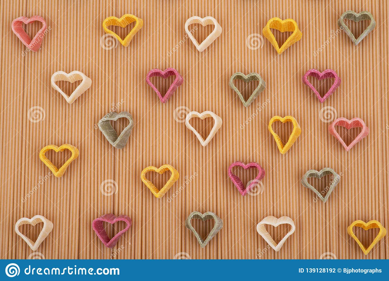 a75b3bd0ab1888 Durum wheat semolina heart-shaped 5 flavors pasta with vegetables arranged  on a brown rice spaghetti pasta background. Valentine`s Day.