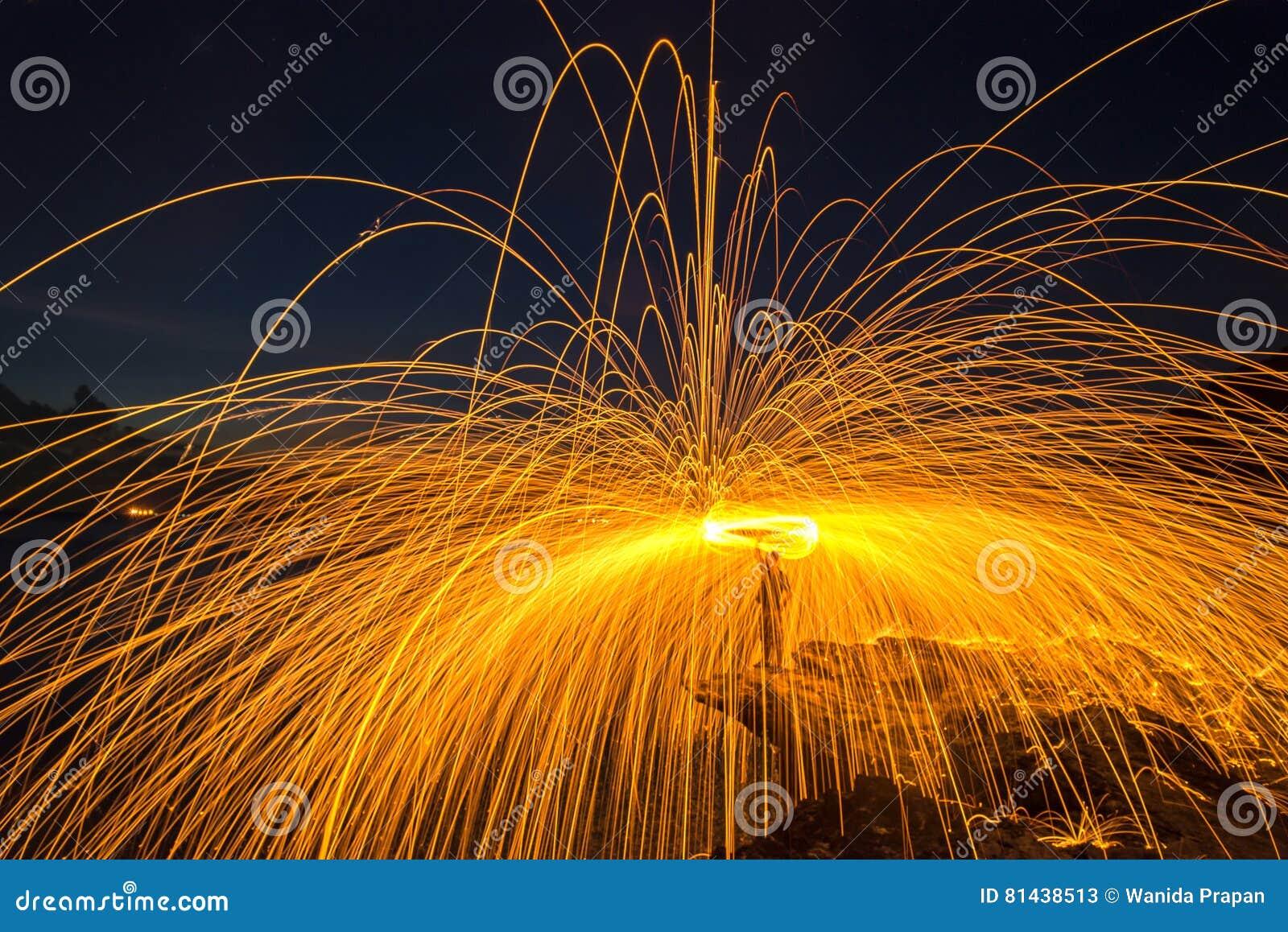 Duschen des heißen Glühens funkt von spinnender Stahlwolle auf dem Felsen
