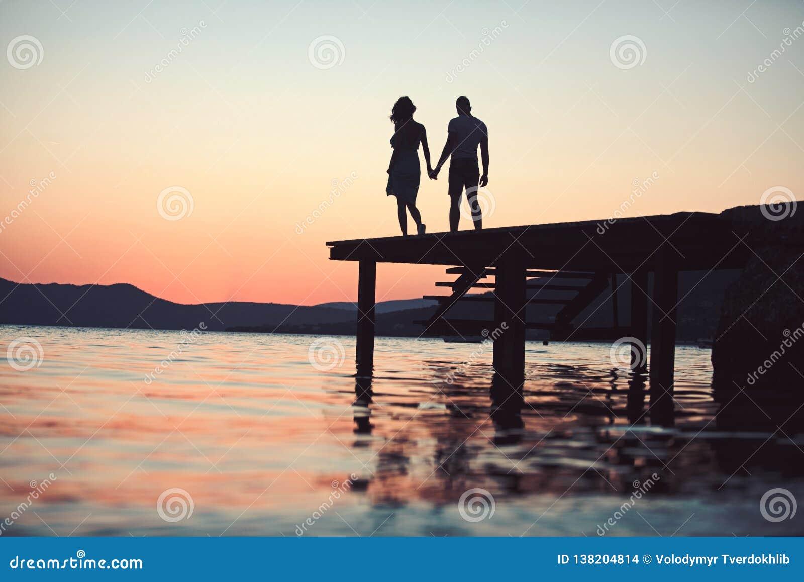 Dusk Couple Silhouette On Pier At Sea Water Dusk Couple