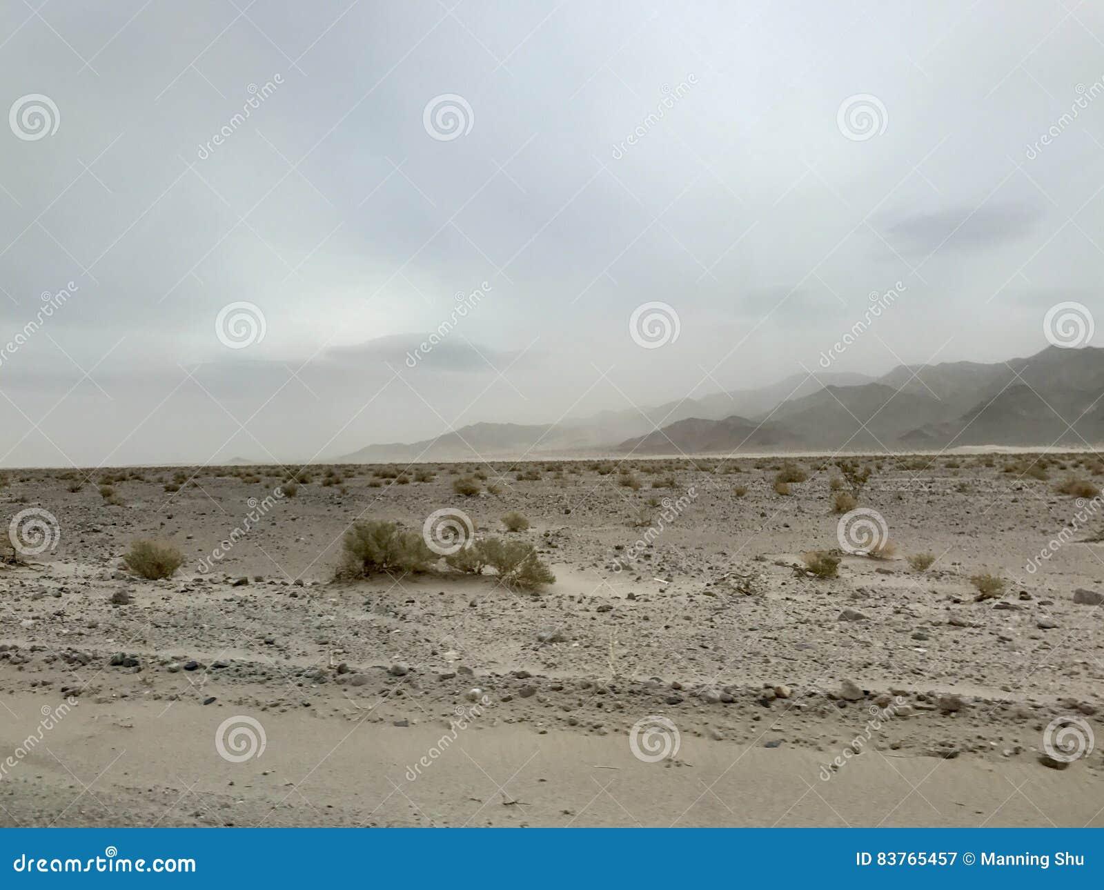 Dusty Storm en desierto con las montañas en fondo
