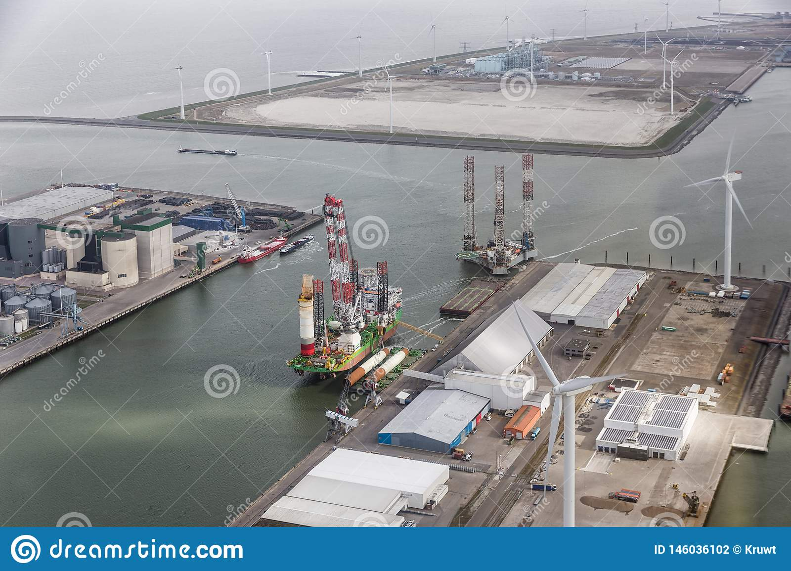 Dutch harbor Eemshaven with wind turbines and offshore construction platforms