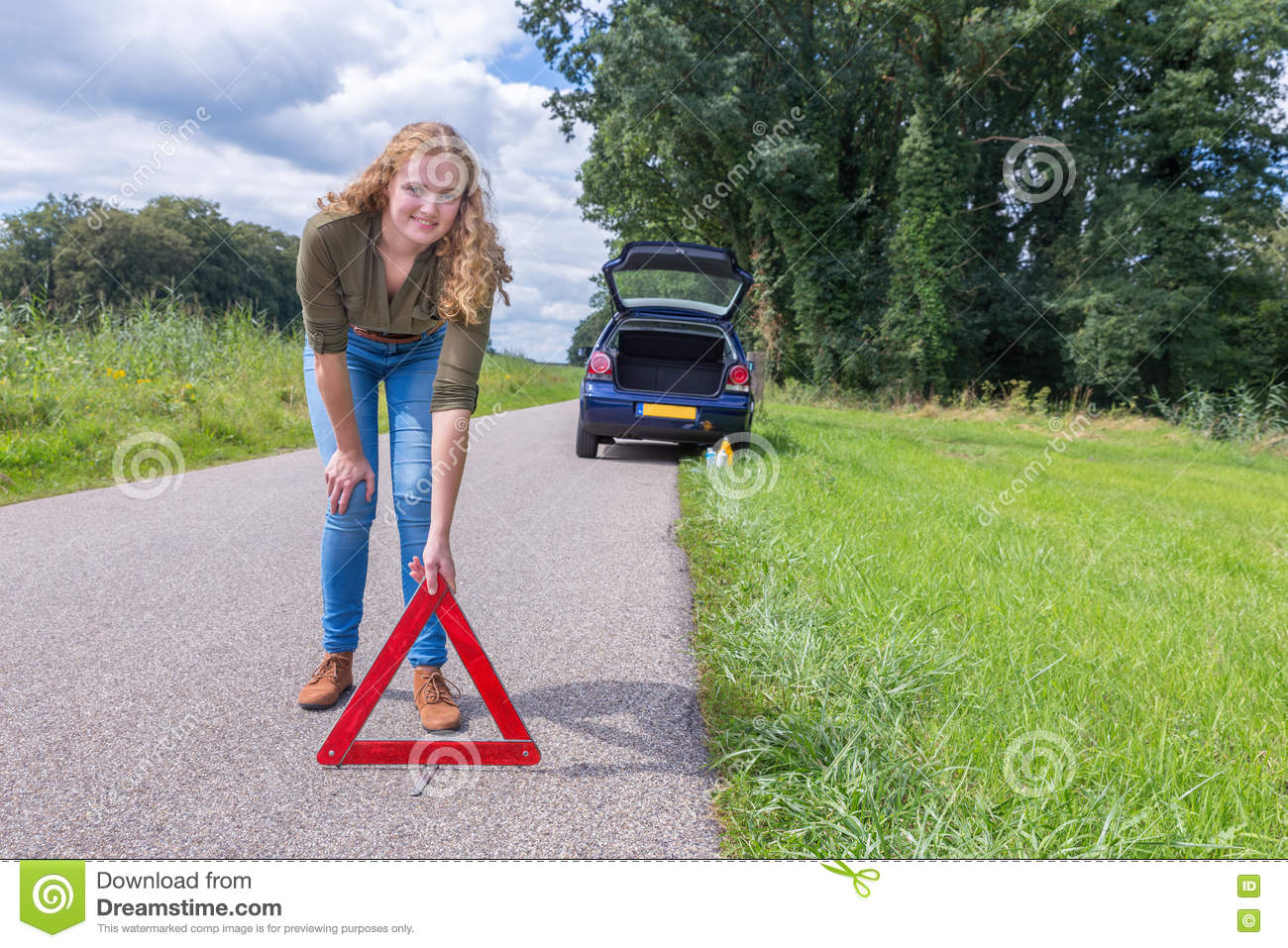 Dutch woman placing warning triangle on rural road
