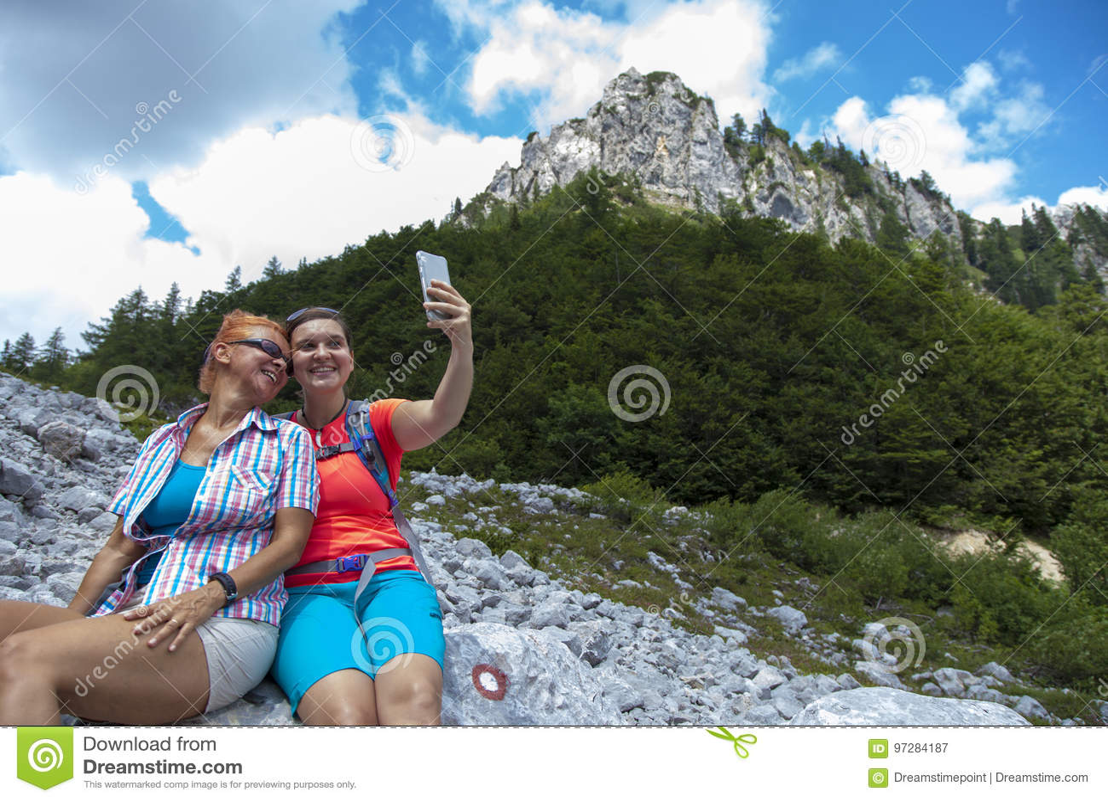 Dwa ładnej żeńskiej kobiety fotografuje selfie na halnym szczycie