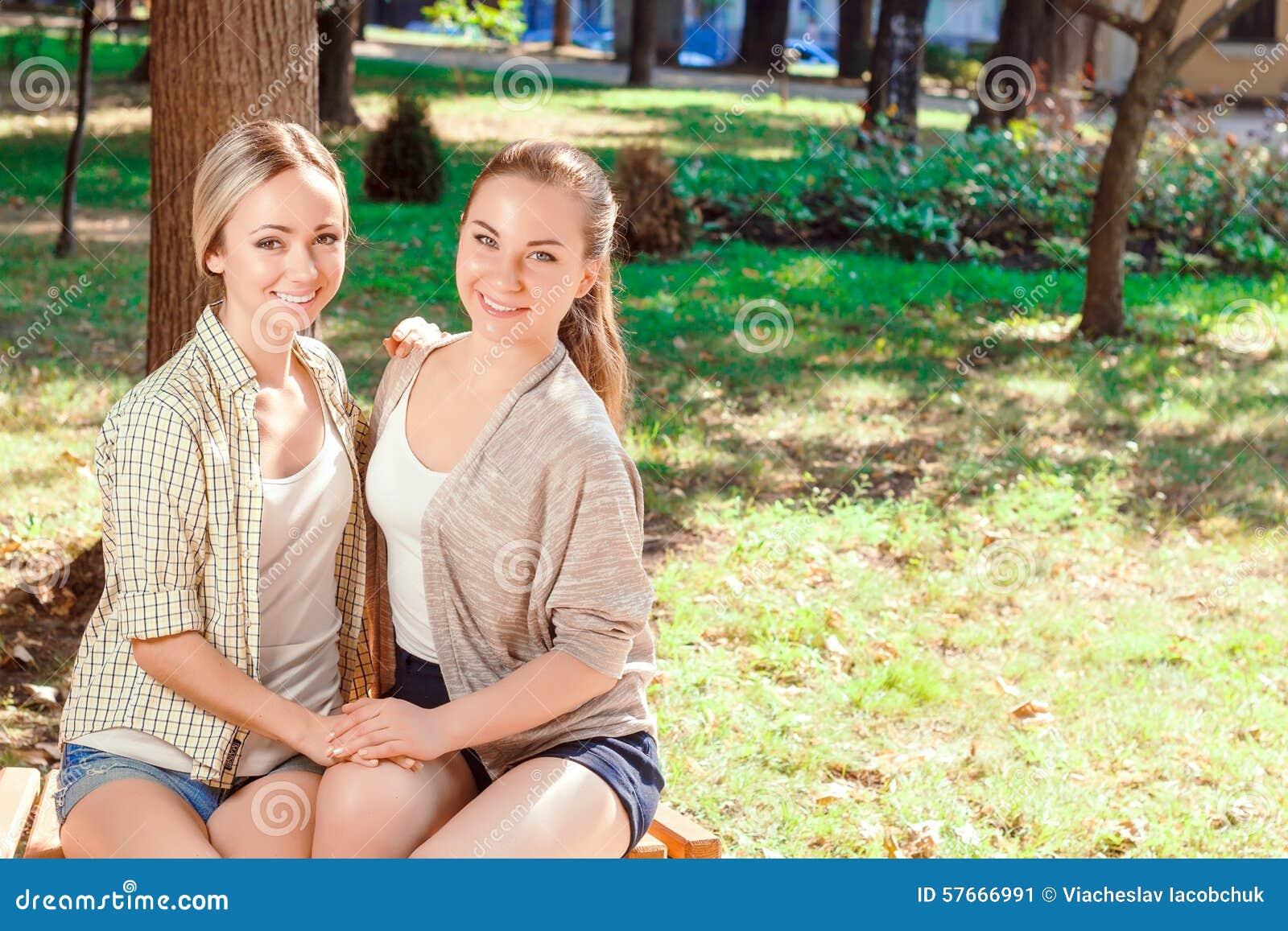 Dwa ładnej dziewczyny siedzi w parku