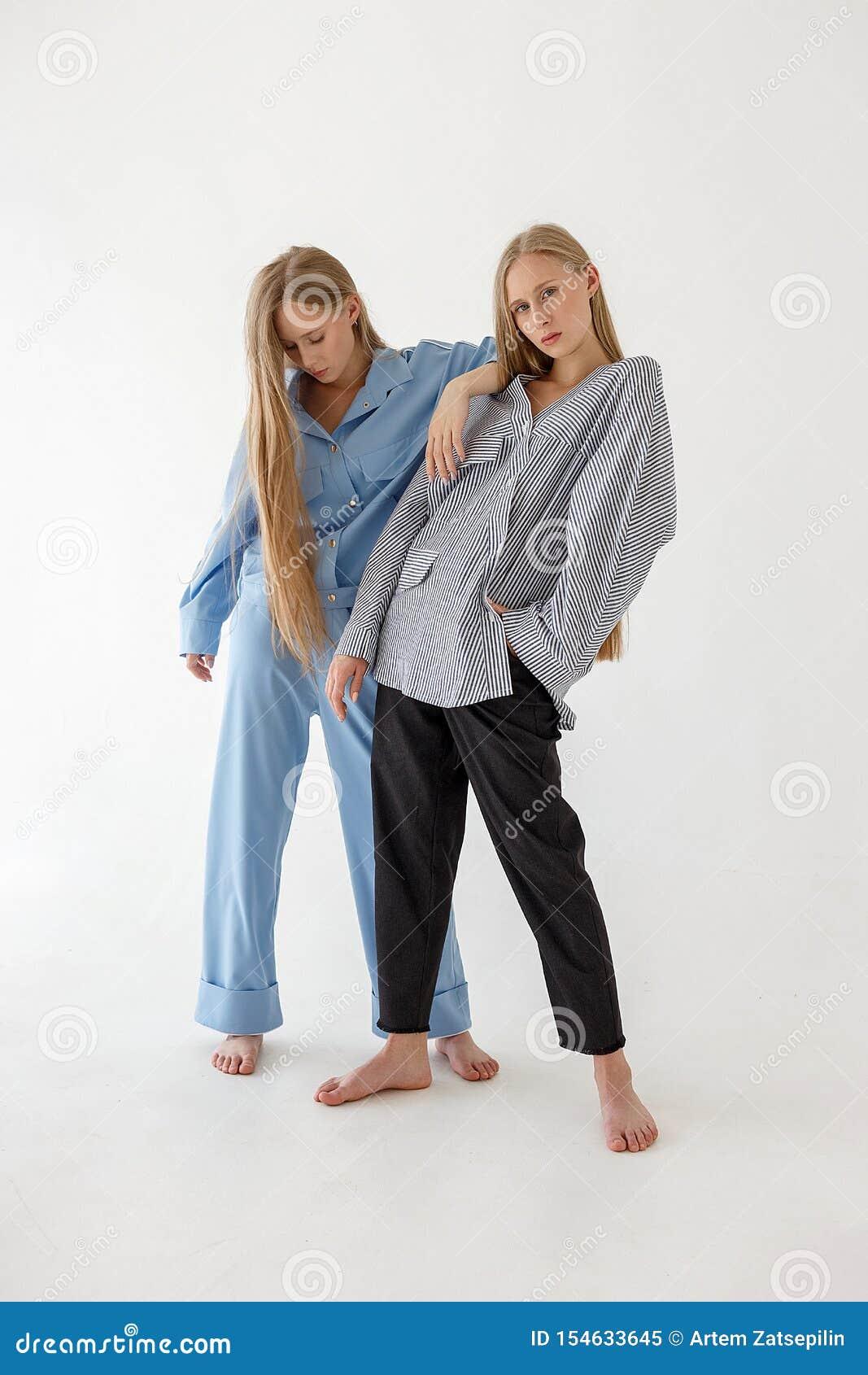 Dwa ładnej młodej bliźniaczej siostry z długim blondynem pozuje na białym tle w ogromnym odziewają Mody photoshoot