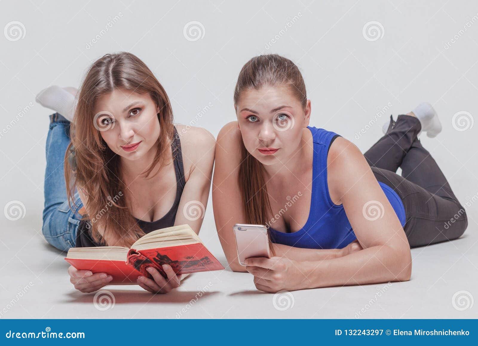 Dwa ładnej młodej kobiety kłaść na podłodze z książką i telefonem komórkowym