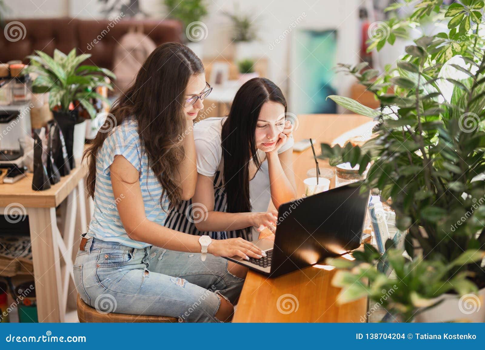 Dwa ładnej szczupłej dziewczyny z długim ciemnym włosy, jest ubranym przypadkowego styl, siedzą przy stołem i patrzeją attentivel