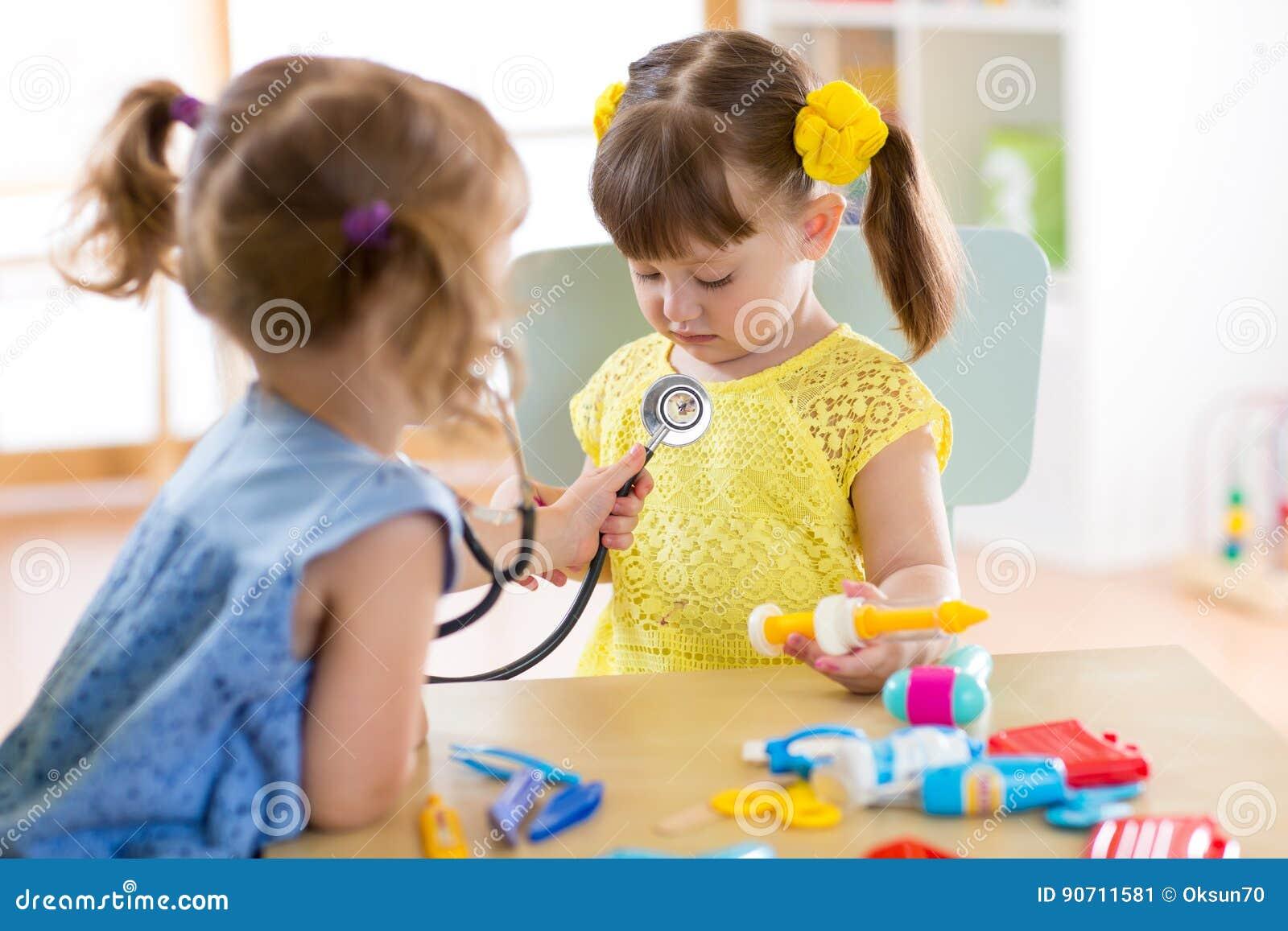 Dwa ślicznego dziecka bawić się lekarkę i szpitalnego używa stetoskop Przyjaciel dziewczyny ma zabawę lub preschool w domu