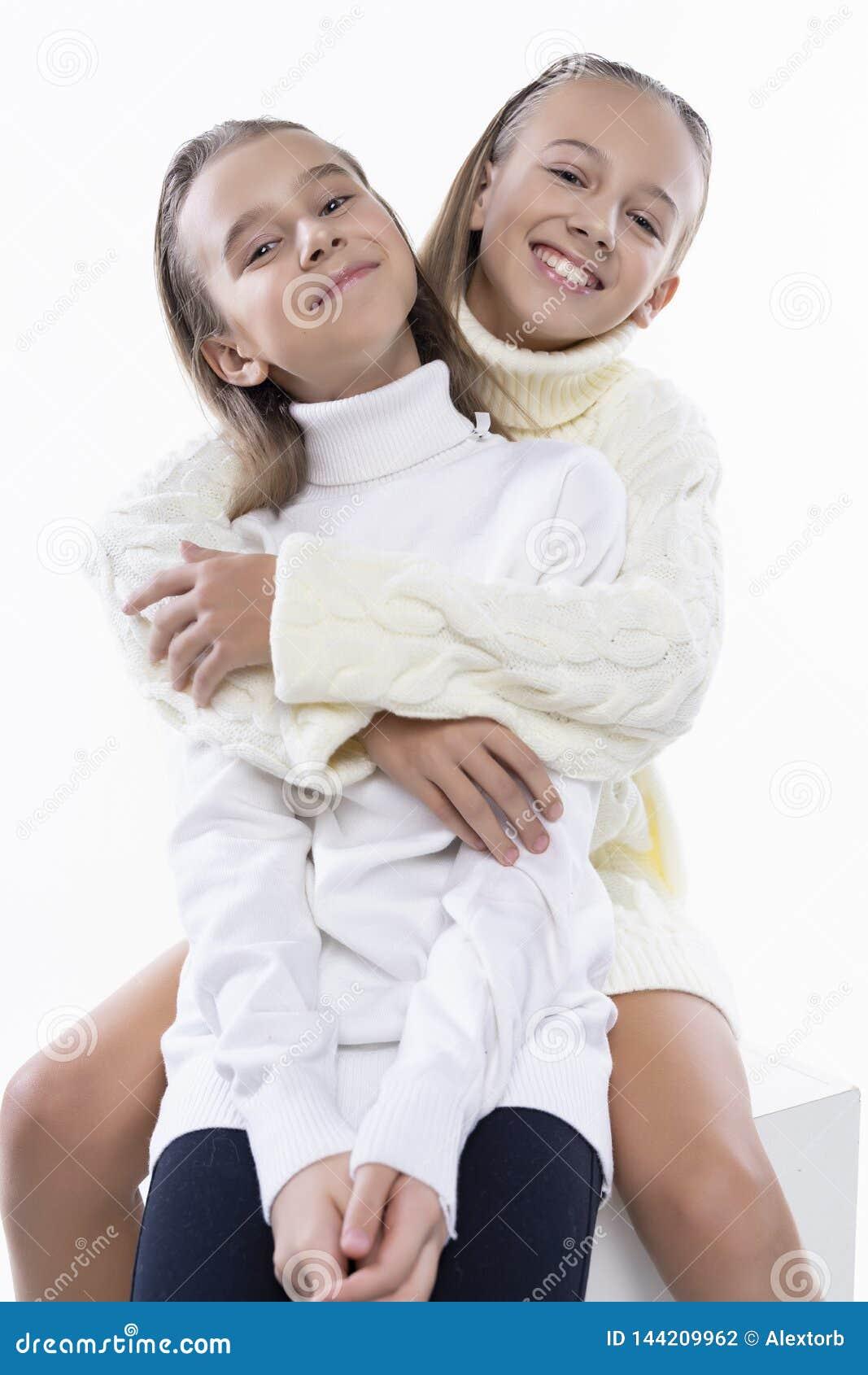 Dwa ślicznej nastoletniej dziewczyny uczennicy jest ubranym białych turtleneck pulowery, ono uśmiecha się siedzą, ściskający each