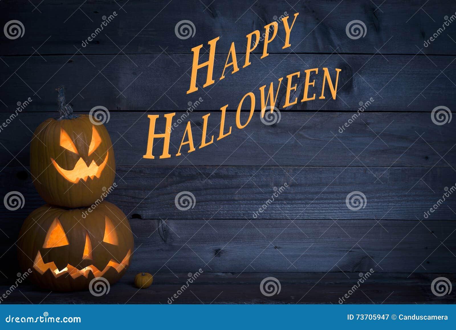 Dwa Ślicznej Zaświecającej bani z Szczęśliwym Halloween Pisać na zmroku - błękitny Nieociosany drewno deski tło