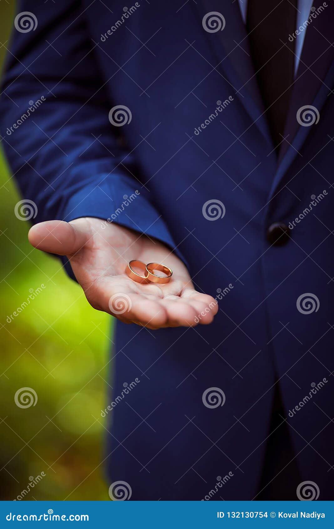Dwa ślubnej złocistej obrączki ślubnej w rękach mężczyzna w górę, nowożeniec, ślubni akcesoria