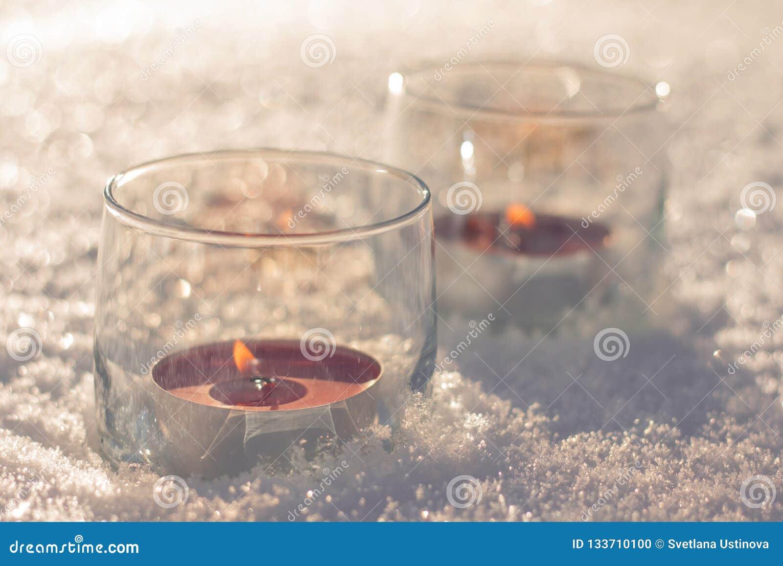 Dwa świeczki w szkłach na śniegu