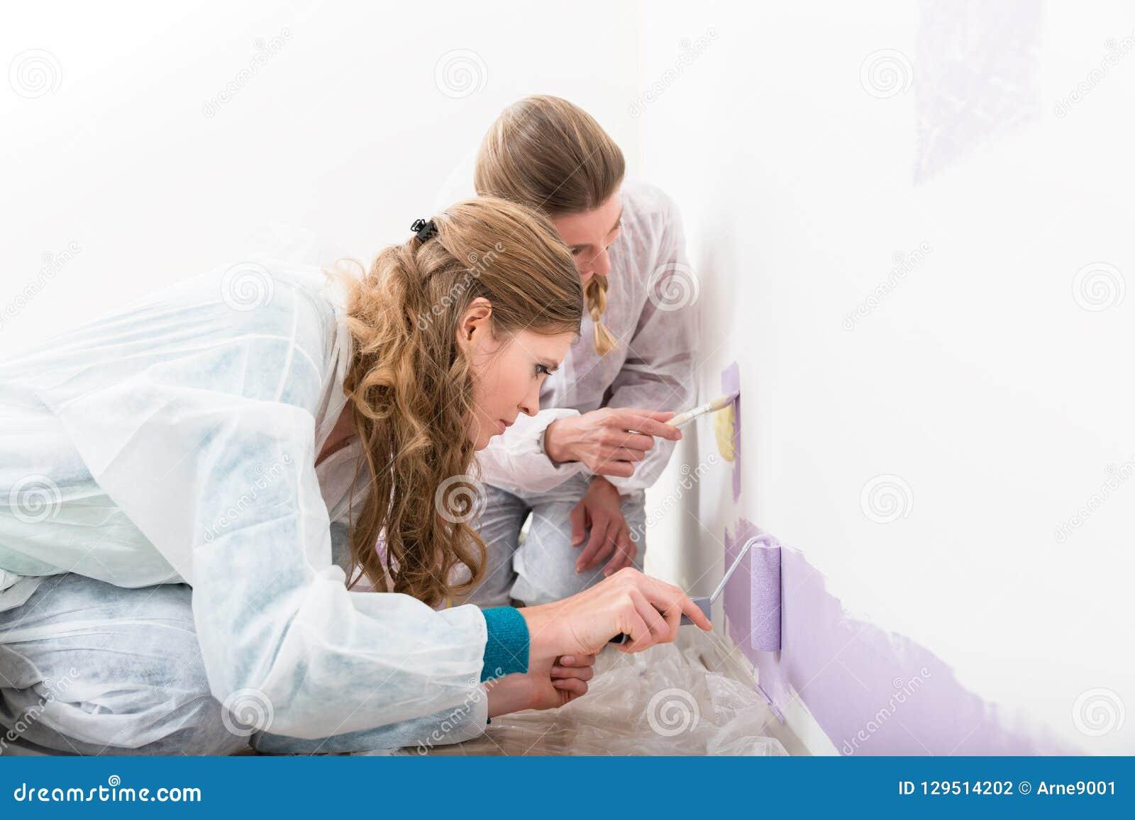 Dwa żeński pracownik daje purpurom barwi na ścianie