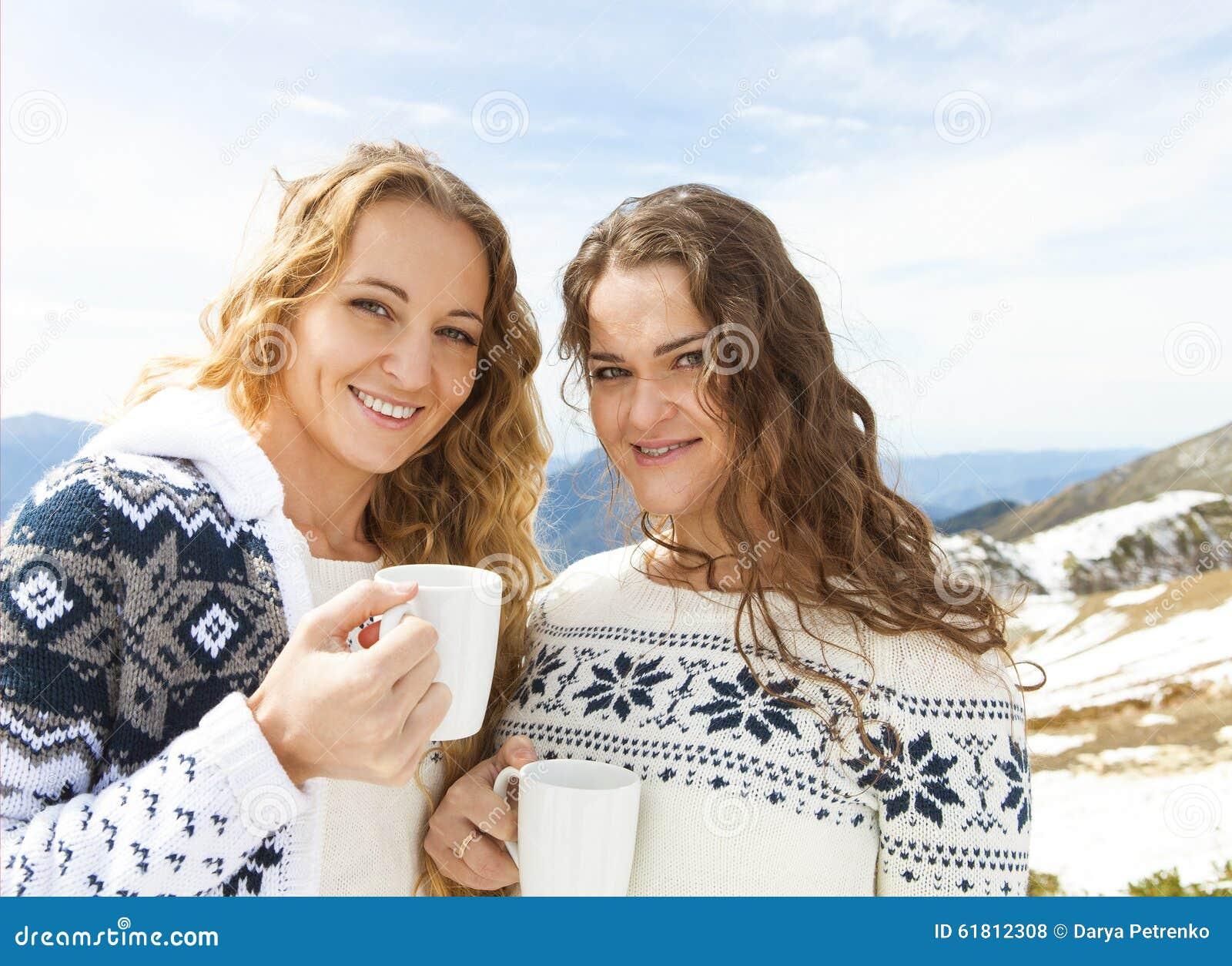Dwa żeńskiego przyjaciela cieszy się gorącego napój W kawiarni przy ośrodkiem narciarskim