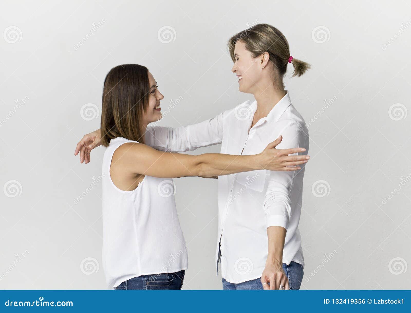 Dwa żeńskiego przyjaciela witają zabawę i mają przy pracownianym backgro