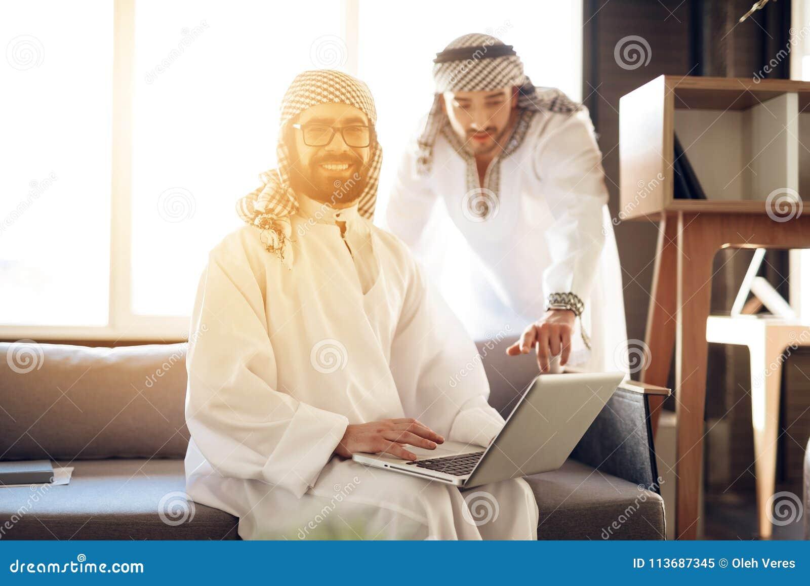 Dwa arabskiego biznesmena z laptopem na leżance przy pokojem hotelowym